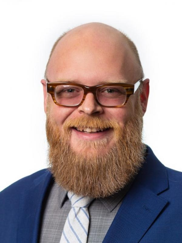 A photo of Bennett Whitaker, a smiling white-presenting person with very short blond hair, a mustache and a medium length beard. Bennett is wearing brown eyeglasses, a bright blue suit coat, a subtle gray plaid shirt and a white tie with narrow blue stripes.